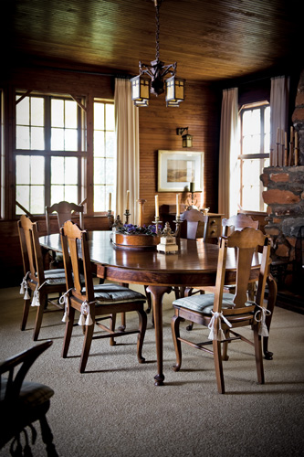 """While the Loughlins' Atlanta kitchen is small (""""It's a drop-in-for-drinks sort of place""""), the couple knew that Tiger Lodge would be the perfect place to host family and friends for big get-togethers. The spacious dining room—complete with a large dining table—provides a welcoming spot for their group to convene over long meals. The Arts and Crafts-style hanging fixture, dining table and chairs were original to the house."""