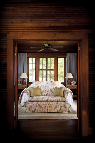 The classic Hickory furniture on the covered porch was original to the house; it once served as the living room furniture of this rustic hunting lodge-turned-mountain retreat.The beadboard that wraps around the lodge's interior was a design signature from day one. When the house was renovated and reconfigured, the beadboard was carefully taken off of the walls, then inventoried and cataloged. Later, it was put back up and re-stained, so the space retains all of its classic qualities, all these decades later.