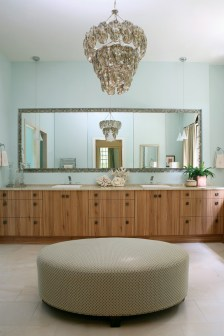 Clean-lined cabinetry from Spain provides plenty of storage with more hidden behind a wall of mirrors. A custom ottoman and chandelier overhead lend an air of elegance while a spacious shower lined with sparkling glass tiles contributes to the ambience.