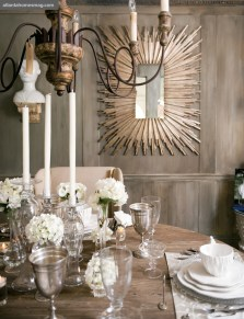 This elegant room at Boxwoods Home features a silver-leafed starburst mirror,an iron-and-wood six-arm chandelier and a carved-wood oval tableset with faux bois ceramic dinnerware.
