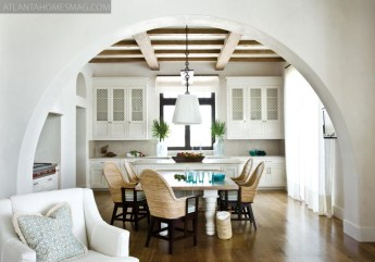 """In designing the kitchen, designer Jackye Lanham carefully considered materials. """"I wanted to be sure that, if someone was in the [adjoining] living room, they were looking back at a pretty space,"""" she explains. To that end, the breakfast table is surrounded by sinuous wicker armchairs and illuminated by a smart-looking custom fixture. Even wall cabinets are detailed with a delicate lattice."""