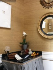 Scalamandre grasscloth covers the walls of the powder room by Scott Reed; framed intaglios, fine etchings and a 19th-century Regency mirror.
