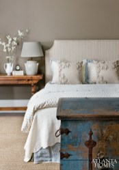 A weathered blue trunk from Lovetrain Antiques, Westbrook's first purchase for the guest room, injects a burst of color into a feminine space that's bathed in soft neutrals, from the custom headboard to the white lamp.
