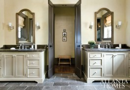 Chocolate-colored flooring and trim provide an Old World contrast against the warm yellow walls of the master bathroom. The creamware accessories are by Waterworks.