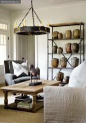 Natural materials and neutral colors, ever the inspiration for designer Jimmy Stanton, are more than apparent in the terrace-level rec room, where earthenware jars fill an iron shelving unit and an old factory gear, crafted into a chandelier, is suspended from the ceiling. A reclaimed wood coffee table and natural linen slipcovers add softness.