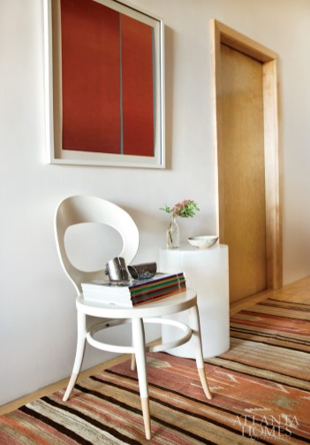 In the hallway, a quietly neutral chair and Italian molded-plastic side table allow the focus to remain on the area rug and the similarly colored wall art.