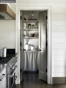 A pretty walk-in pantry, with open shelving and quaint skirt-covered storage, leads to an outdoor grilling patio.