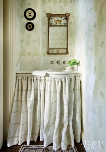 Tucked under a stairwell, the powder room is prettied up with linen skirting, graphic wallpaper and a Federal mirror.