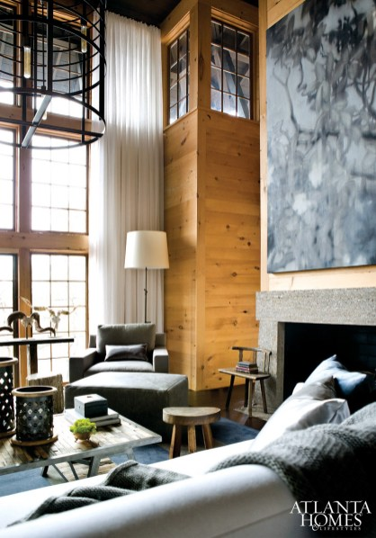 """Commanding attention above the stone fireplace is """"Magnolias,"""" a Michael Dines painting that Ferrier considers a """"modern way of looking at trees."""" Equally striking is Coup d'Etatâ's Silo light fixture, fabricated from rusted and weathered hay balers. Both pieces help fill the room's expansive volume of vertical space."""