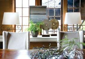 Atop a glamorous credenza upholstered in faux leather is a tableau of found objects. Mounted millstones impart rusticity to the vignette while one of a series of framed gray driftwood pieces is hung on the window frame.
