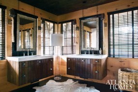 Ferrier is a fan of hides, not only for their durability but also the way their organic shapes play off of a room's linear planes. Here, one is used as a rug in the master bathroom. Wood branch sconces from Design Galleria Kitchen & Bath Studio illuminate metal-framed mirrors by Stonehenge.