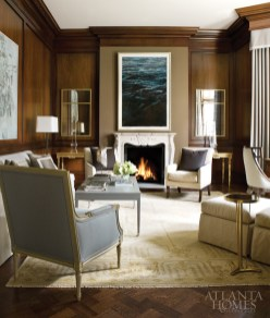 Challenged by the study's dark paneled walls, Brown brought light into the room through his use of mirrors, acrylic accessories and a pale-toned rug from Rugs by Robinson. The designer crafted a more modern backdrop for artist Liana Repass' pastel on paper—hung above the mantel—by wrapping the chimney breast in a Phillip Jeffries sateen fabric.