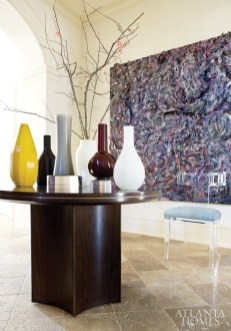 Designer Robert Brown is taken with artist Robert Kuo's Peking Glass vases, especially when grouped en masse on a McGuire table in the foyer. Depending on the season, flowers or branches are often displayed in them. The painting is by Thornton Dial. The Lucite chair is by Geoffrey Bradfield, available through Travis & Company.