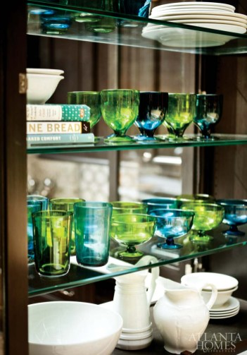 Built-in glass shelving holds colorful glassware.