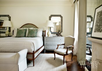 Lamps from Baker flank a bed by Hickory Chair. The mirrors feature shagreen-like frames.