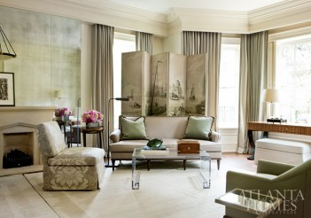 A soft color palette and sumptuous textiles envelope the master bedroom. The sofa is covered in a Rogers & Goffigon fabric, while the A. Rudin slipper chair is upholstered in a damask by Romo. Paired with a Lucite cocktail table from Travis & Company, the pieces create an intimate sitting area. The screen is from William Word Antiques, and the room is anchored by a rug from Stark Carpet.