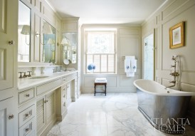 Elegant Calcutta Gold marble on the floor and in the shower creates a unified look in the brand-new master bathroom. A stand-alone tub from Waterworks makes the room as elegant as it is relaxing. A painting by Pierre Bittar hangs on paneled walls designed by Pak Heydt & Associates.