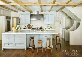 """The original kitchen was more utilitarian. The renovated space—which now includes a new kitchen, breakfast area and family room, all of which open up to each other—needed to suit the modern needs of a busy family of six. """"This is the part of the house the family really lives in,"""" says Connor. The kitchen cabinets are painted in Farrow & Ball's Pigeon. The range is by La Cornue and the stools are from English Accent Antiques."""