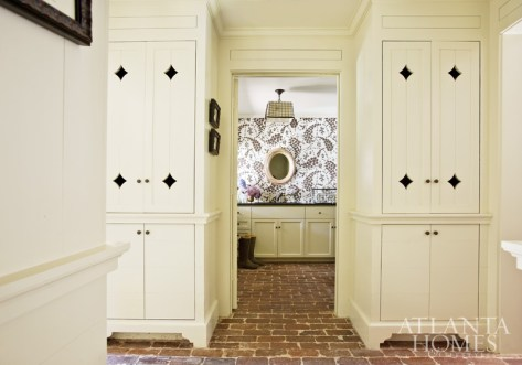 Exquisitely designed locker-style cabinets keep clutter to a minimum just outside an unexpectedly chic laundry room. Wallcovering, China Seas.