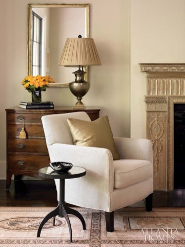 A comfortable club chair from Bungalow Classic mixes company with a classic antique chest from ABC Carpet and Home and the more modern shaped drinks table from Mathews Furniture Galleries. The mirror and metal lamp are from Scott Antique Markets.