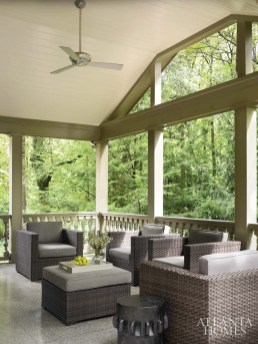 """Previously unused by the homeowners, the porch now beckons with a vaulted ceiling and calming terrazzo floors. """"You really feel like you are up in the trees,"""" says Webb. Woven outdoor furniture and cushions by Aventis. End table, Bungalow Classic."""