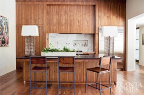The kitchen, which boasts ample storage space both beneath the island and on either side of the integrated hood, opens to the family room and breakfast area. The statuary slab on the backsplash reveals a small recessed niche for key ingredients and utensils.