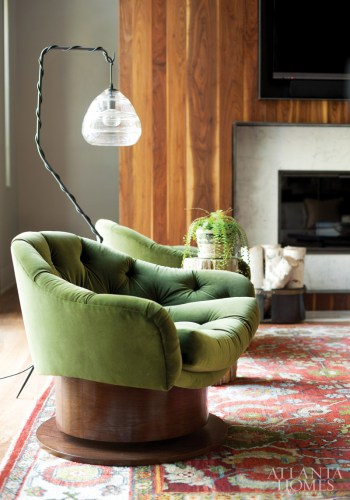 A pair of tufted velvet Coup d'etat swivel chairs graces the living room.