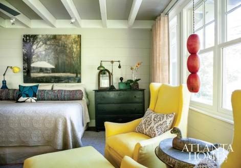 """The master bedroom is a prime example of how the owner and designer worked as one. """"Ann and I have a mutual love of natural stone and off-white tones combined with rock, and reclaimed wood mixed with metals,"""" says Jones. """"The jolts of color in the tile, furnishings and artwork sing against the natural palettes. It's truly a signature of the two of us when we work together."""" Yellow chairs, South of Market. Pendant light made of buoys, Jeff Jones Design. Bedside lamps, Pollen. Painting by Courtney Garrett."""