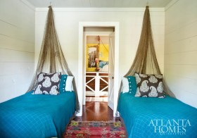 The space is outfitted with twin beds covered in Utility turquoise blankets and matching shams, while fishing nets suspended from the ceiling create the illusion of headboards.
