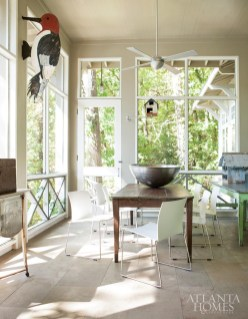 Modern white chairs from Domus International pull up to a primitive dining table at one end of the screened porch; Jones added the wall-mounted woodpecker, playing to Ann Veal's preference for a modern/primitive mix.