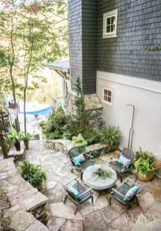 A flagstone-lined sitting area, with gardens designed by Tim Stoddard, features comfy seating and an outdoor shower. The chairs are from Kolo Collection.