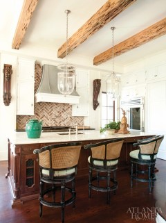 "In the kitchen, designed by Spitzmiller & Norris, the hewn beams of pecky cypress are each carved out of a single massive tree trunk, hundreds of year old, which was raised out of a swamp. ""I really appreciate how special that is,"" says homeowner Courtney Amos. ""It's very hard to find those types of indigenous materials."" The bell jar lanterns are available through Grizzel & Mann. Barstools, Smith Grubbs & Associates. Refrigerator and freezer, Sub-Zero."