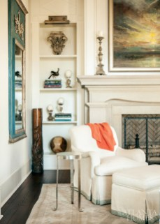 The color in the trumeau mirror from Parc Monceau relates perfectly to the blues in the living room fabrics. Propped in the corner, the 1880s wood carving of a dolphin that designer Carole Weaks found in France may have originally functioned as the leg of a fireplace surround. Chairs are from Edward Ferrell + Lewis Mittman and feature a Brunschwig & Fils fabric. A Greg Gustafson canvas from Tew Galleries hangs above the mantel. Bookcase lights, Circa Lighting.