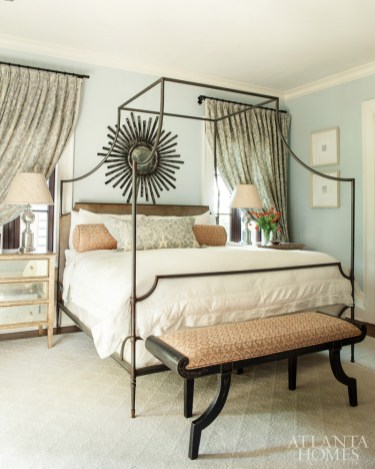In the master bedroom, Benjamin Moore's Blue Lace paint color blankets the walls. The bed, mirrored chest and bench are by Niermann Weeks, available through Grizzel & Mann. The bench is upholstered in a Fortuny fabric. A mirror from Amy Howard Collection is from Bohlert Massey Home.
