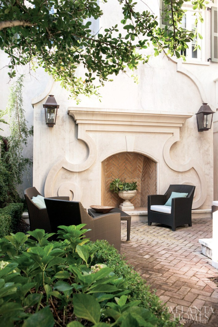 """""""We wanted the fireplace sitting area to draw people out for picnics or cocktails,"""" Spitzmiller adds. Cast-stone mantel and face veneer designed by Spitzmiller and produced by Cutting Edge Stone. The furniture is by Janus et Cie. """"Every way you approach the house you get a beautiful view of the courtyard,"""" says designer Susan Massey."""