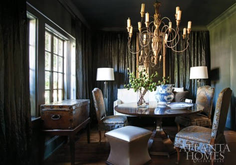 """An artfully arranged collection of creamware and pewter adds to the play between darks and lights in the dining room. """"Susan is the best colorist in the business,"""" says Prillaman, who, after she had already enlisted Ferrier for the project, pored through a file of inspirational tear sheets only to find that most of them were the designer's projects. Ferrier chose a midnight blue hue—Benjamin Moore's Westcott Navy—for the room's walls and ceiling to complement the gorgeous woods from Prillaman's antiques. The chairs are upholstered in a damask by Nobilis."""