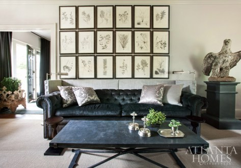 Designer Susan Ferrier's deft design hand—and balancing act—is evident in homeowner Mary Prillaman's living room, where a collection of charcoal botanicals anchors an elegant seating arrangement that includes a commanding Holland & Company Chesterfield sofa. An upholstered screen frames it, adding texture and dimension to the space.