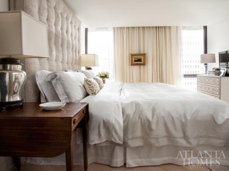 Ingram's well-edited approach is readily apparent in the bedroom, where a king-size bed, with a luxurious to-the-ceiling upholstered headboard, is joined by little more than a nailhead chest of drawers and a pair of antique Pembroke tables.