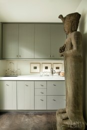 The kitchenette is home to a Mayan statue that Morris found at Lush Life. The three photographs are by Masao Yamamoto.