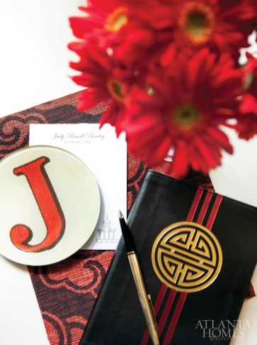 "A ""J"" plate from John Derian & Co. and Bentley's notebook, pen and notepads with name and pagoda symbol designed by Alston Wise rest on a Schumacher wallpaper."