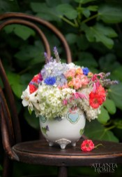 A petite Japanese sugar bowl features Annabelle and Mophead hydrangea, as well as coral roses, cornflower, lavender, honeysuckle and gardenia.