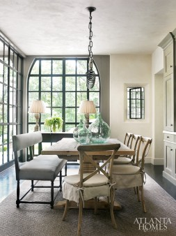 The steel window-wrapped breakfast room stirs a French-country feel with bistro chairs from Bungalow Classic tucked beneath a reclaimed wood table from Restoration Hardware. Upholstered bench, Artistic Frame. Iron chandelier, Dessin Fournir. Rug, Stark Carpets.