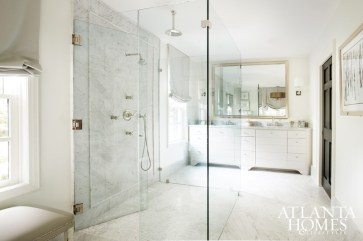 The glass shower disappears among the white marble-covered master bath. A gilded mirror holds court above his and her vanities, adding an elegant touch.