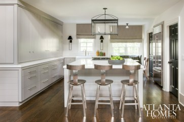 Morris gutted the original kitchen, installed a white marble-top island and raised the cabinetry to the ceiling to give the illusion of space. The barstools are from Go Home, Ltd.; the lantern and sconces are by Averett through R Hughes.