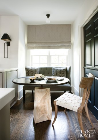 In lieu of statement lighting in a kitchen breakfast nook, a modest light bulb suits the small space, created with an upholstered bench from B.D. Jeffries and a wood-and-metal dining table from Stanton Home Furnishings.