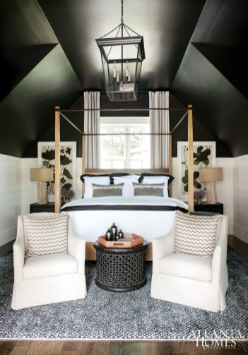 To bring out the room's architectural bones, Morris bathed the guest room above the garage in black paint, which influenced the design direction, including the selection of a pair of Susan Hable floral paintings from Bungalow to chests from Stanton Home Furnishings and a wooden ottoman by B.D. Jeffries. A canopy bed by Lillian August from the Mercantile helps structure the arrangement, while a pair of club chairs from Bungalow Classic lighten up the space.