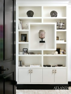 In the master bedroom vanity area, a subtle built-in is filled with the homeowner's collection of silver and objets d'art, including a carved bust of the Goddess of Mercy from Burma at center.