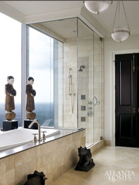 In the master bathroom, a set of wooden Burmese monks and a pair of bronze elephants found at PierceMartin accentuate the natural stone tiles.