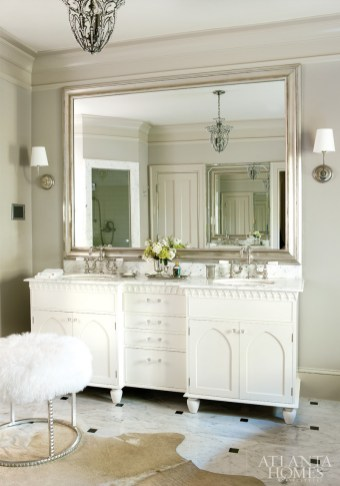 In the master bath, an existing vanity complements the strong architecture seen throughout the home. The charming wooly stool-perhaps Mason's favorite object in the whole house-was sourced from Emporium Home.