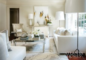 """The living room features a pair of tall iron floor lamps by Amy Howard Home that flank a white sofa custom designed by Atlanta's Bjork Studio. Low-slung but deep, it sidles up to a custom mirrored cocktail table handcrafted by a North Carolina artisan and a silk rug from Designer Carpets that designer Barbara Heath likens to """"a typography shot in silvers and ivories."""""""